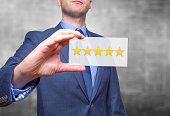Businessman hand holding five stars isolated on grey background. Business rating concept. Stock Photo