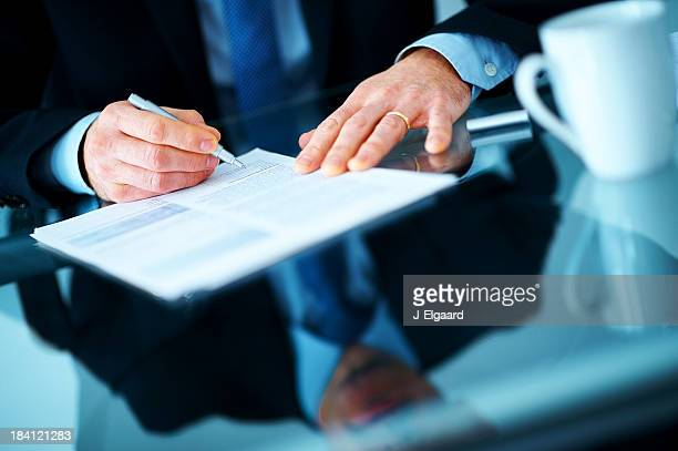 Businessman hand signing contract paper at the desk