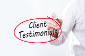 Businessman Hand Writing Client Testimonials with a marker over transparent board,  Business concept.