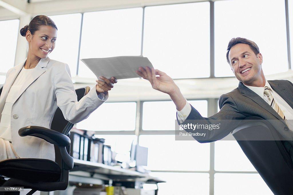 Businessman handing co-worker paperwork in office : Stock Photo