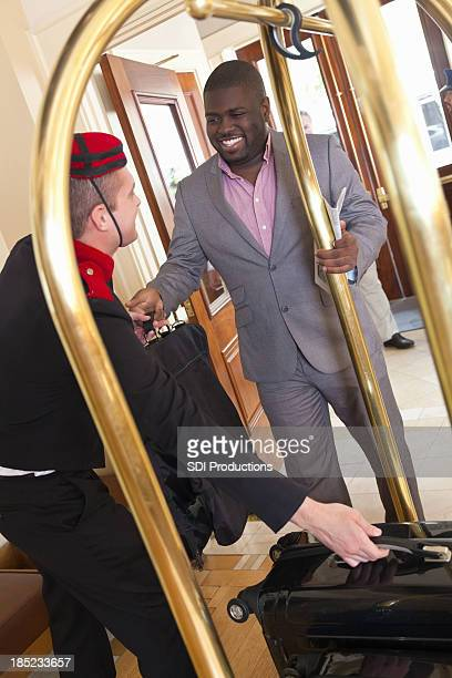 Businessman handing luggage to bellhop while checking into nice hotel