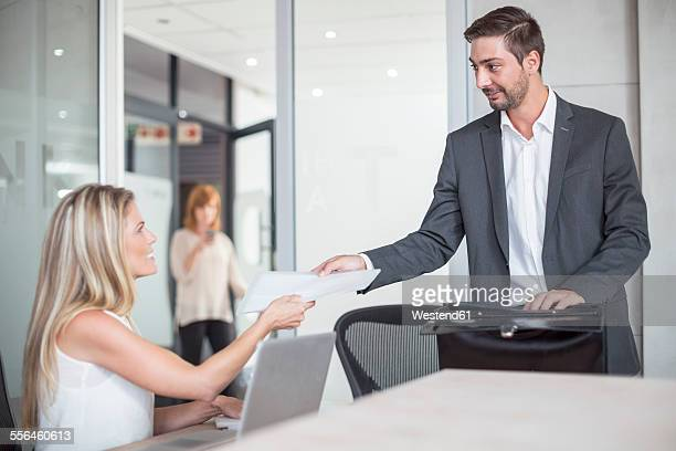 Businessman handing out documents in conference room