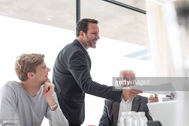 Businessman handing over documents in conference room