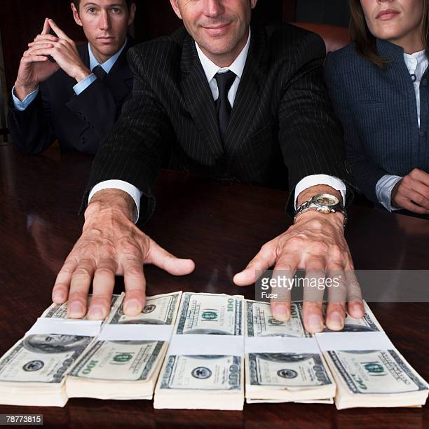Businessman Handing over Dollar Bills
