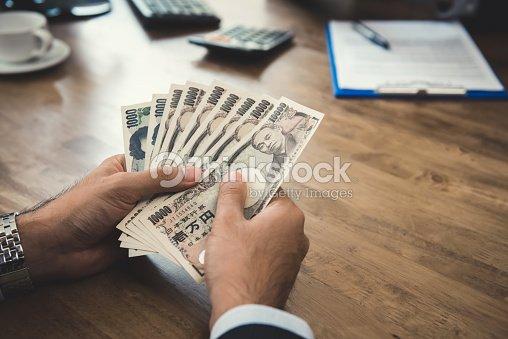 Homme daffaires mains compter largent des billets dyens japonais au