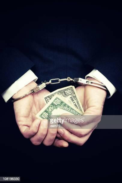 Businessman Hands in Handcuffs Hold Ten Dollar Bill