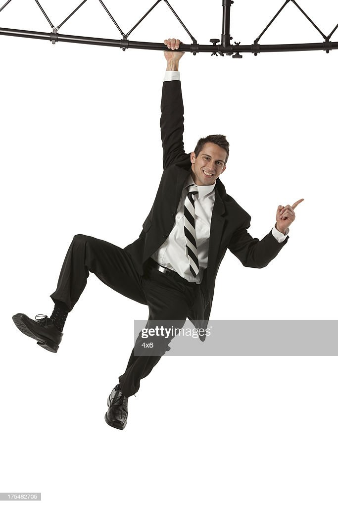 Businessman hanging from a metal structure