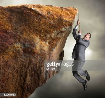 Businessman hanging from rope off of a cliff