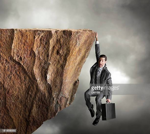 Businessman hanging on for dear life from edge of cliff