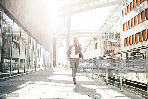 Businessman having a call outside office buildings
