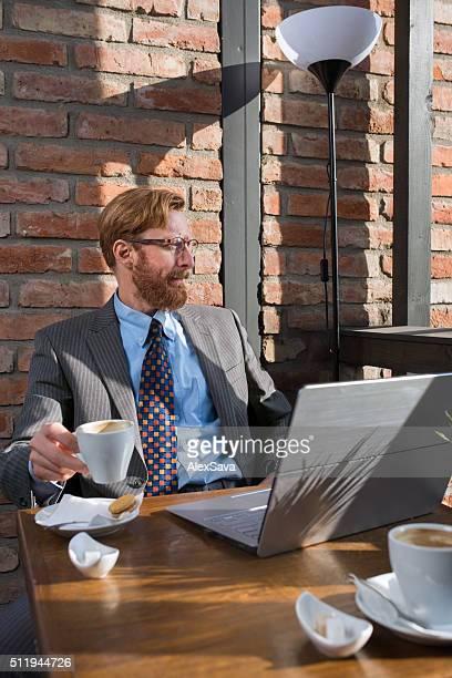 Businessman having a coffee break  on a sunlit terrace