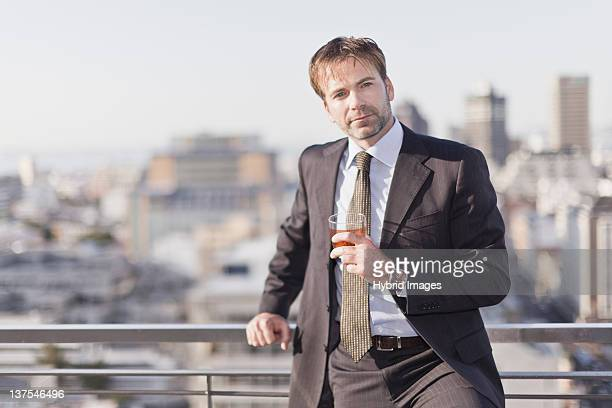 Businessman having a drink on rooftop