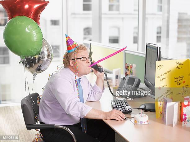 Hombre de negocios teniendo una fiesta de cumpleaños en escritorio