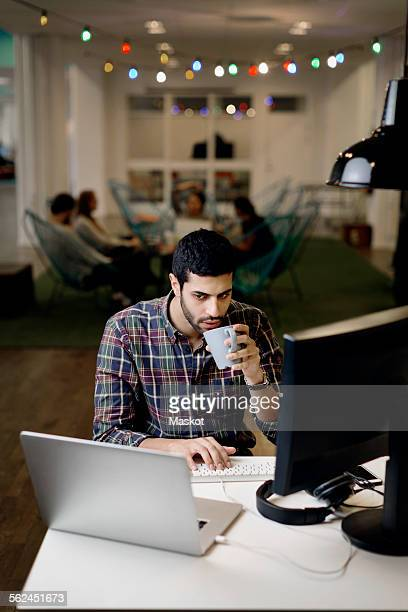 Businessman having coffee while working late in creative office
