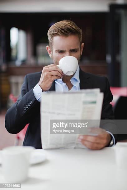 Homme d'affaires ayant café avec journal
