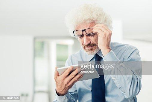 Businessman having eyesight problems : Stock Photo