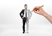 Businessman having the left half a real man and the right half a picture that is drawing with a pencil held in someone's hand. Creating a successful man. Starting a business from nothing. Image making