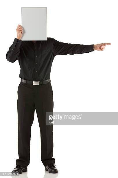 Businessman hiding his face with a placard and pointing
