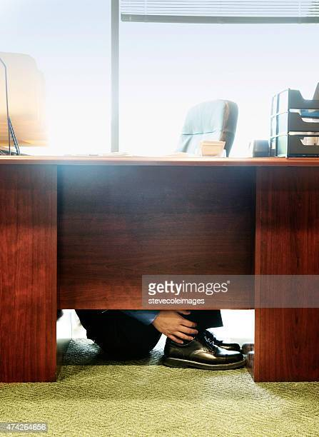 Businessman hiding under desk at office.