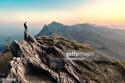 businessman hike on the peak of rocks mountain at sunset : Stock Photo