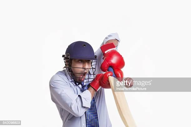 Businessman hitting ball over white background