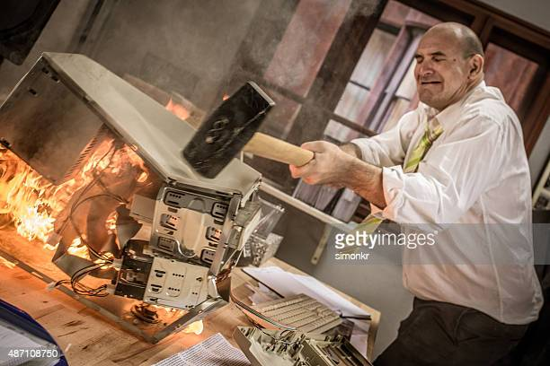 Businessman hitting hammer on burning CPU