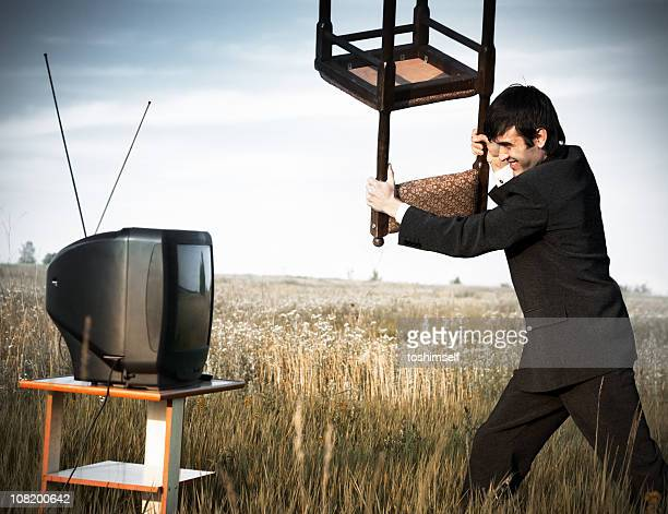 Businessman hitting the TV