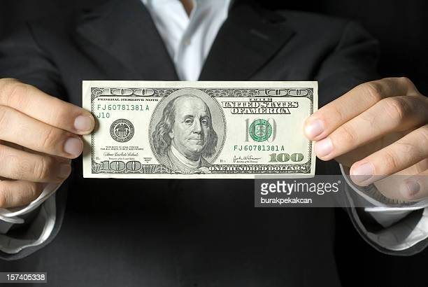 Businessman holding $100 US note