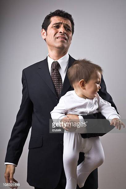 Businessman holding a baby