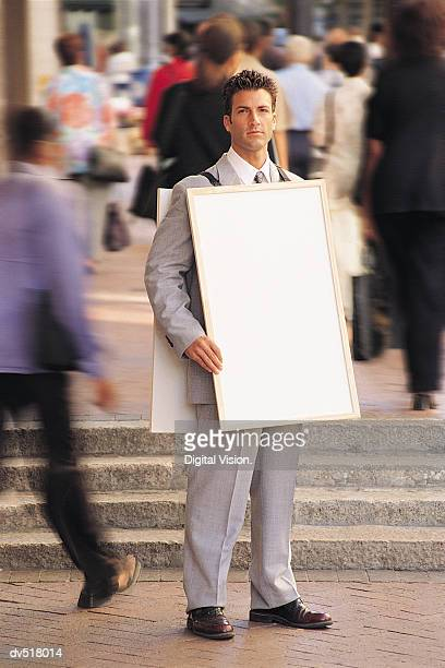 Businessman holding a blank board