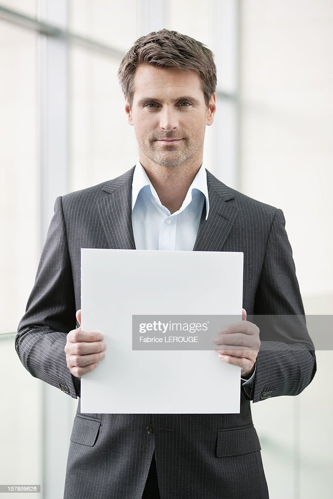 Businessman holding a blank placard in an office : Stock Photo