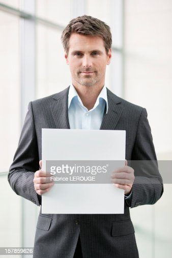 Businessman holding a blank placard in an office