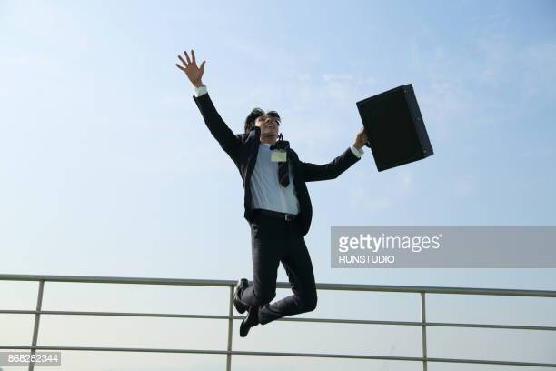 businessman holding a briefcase and jumping