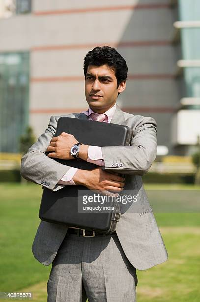 Businessman holding a briefcase and thinking, Gurgaon, Haryana, India