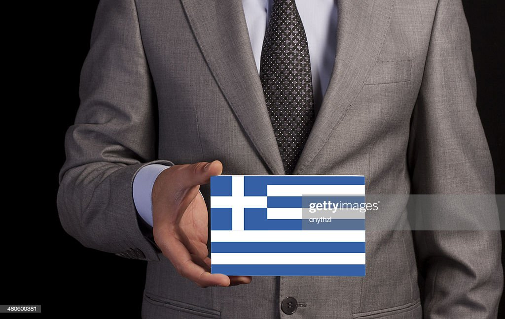 Businessman Holding a Card with GREECE Flag : Stock Photo