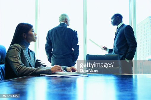 Businessman Holding a Document Listening to a CEO in a Conference Room