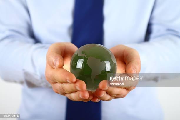 A businessman holding a green globe
