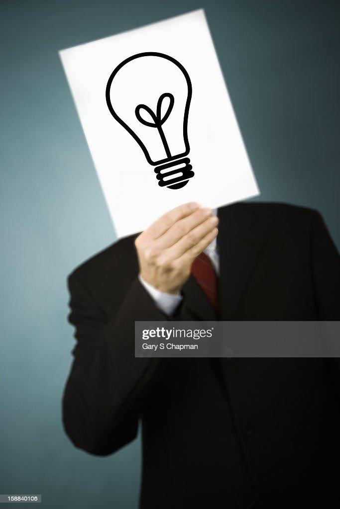 Businessman holding a lightbulb drawn on a card : Stock Photo