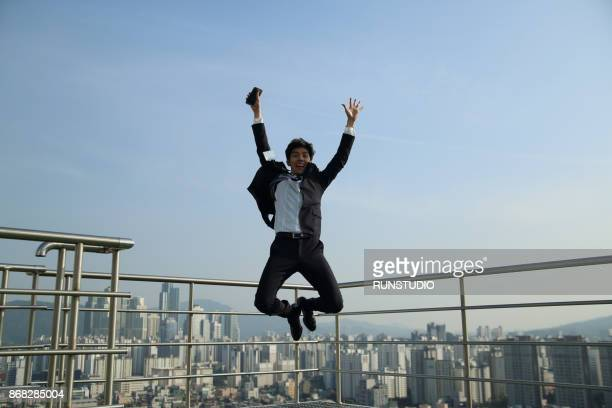 businessman holding a mobile phone and jumping