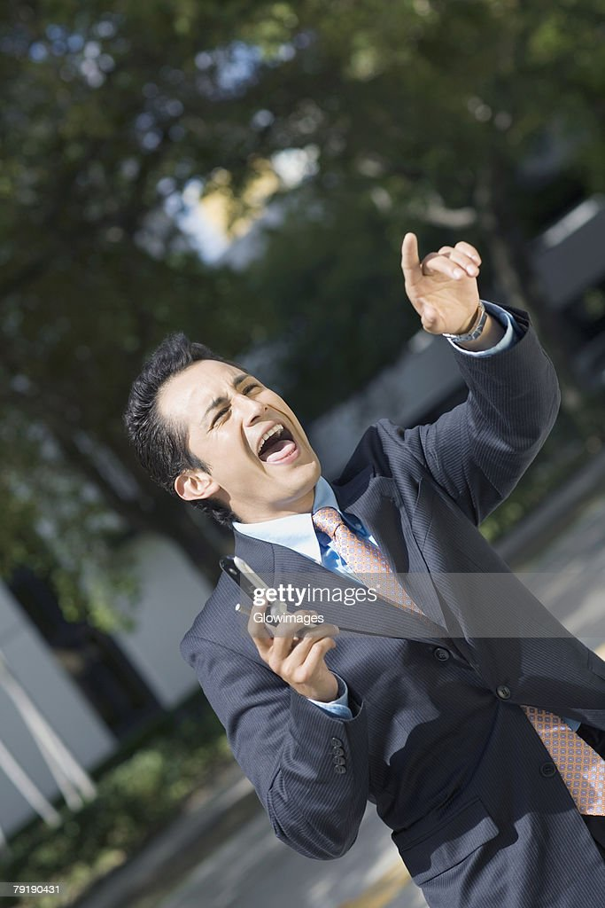 Businessman holding a mobile phone and shouting : Foto de stock