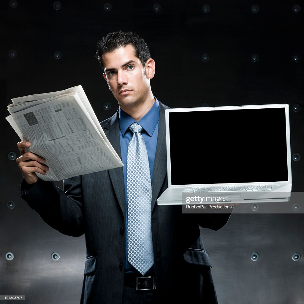 businessman holding a newspaper and a laptop : Stock Photo