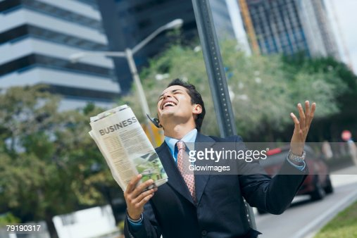 Businessman holding a newspaper and smiling : Foto de stock