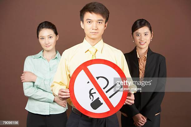 A businessman holding a No Smoking sign and standing with two businesswomen.