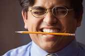 Businessman holding a pencil between his teeth
