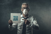 Businessman wearing a mask and polluted air, he is holding a sign with fresh air advertisement