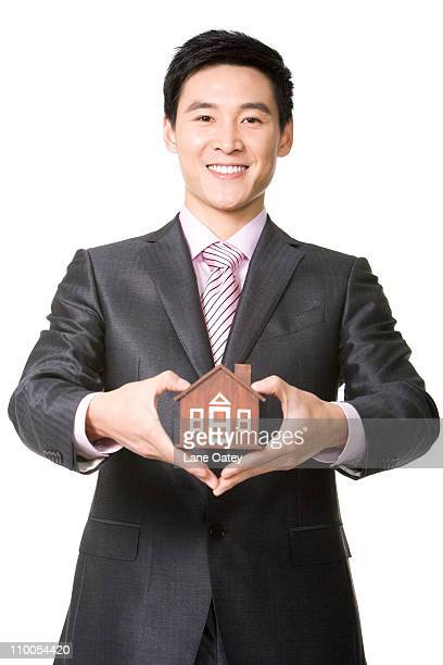 Businessman holding a small wooden model home