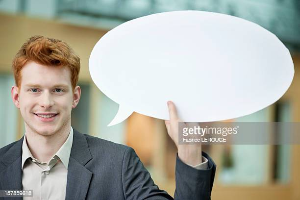 Businessman holding a speech bubble and smiling in an office