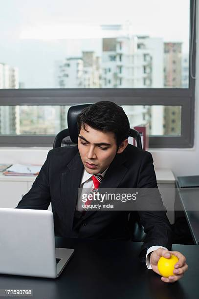 Businessman holding a stress ball and looking at a laptop