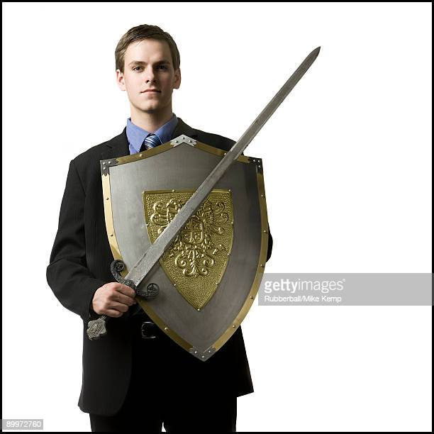 businessman holding a sword and shield