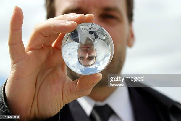 Businessman holding a transparent globe.